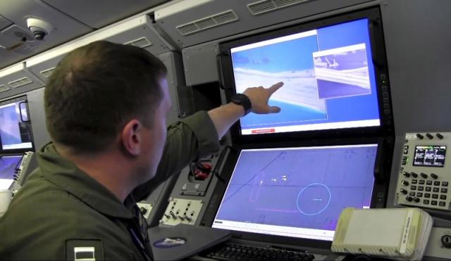 A U.S. Navy crewman aboard a P-8A Poseidon surveillance aircraft views a computer screen purportedly showing Chinese construction on the reclaimed land of Fiery Cross Reef in the disputed Spratly Islands May 21, 2015. REUTERS/U.S. Navy/Handout via Reuters