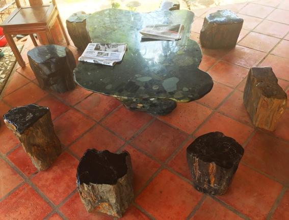 Bộ bàn ghế làm bằng gỗ hóa thạch đặt hờ hững ở góc sân