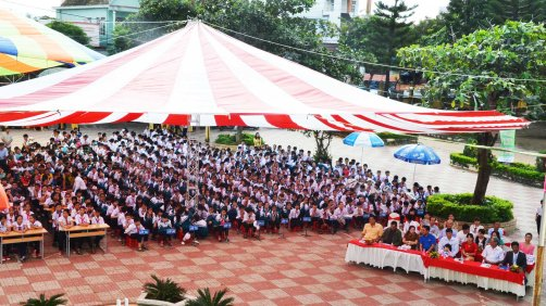 Khách mời và học sinh ngồi dưới bóng mát của những chiếc dù